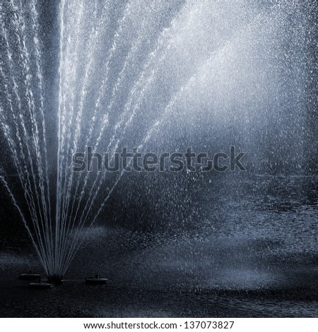 fragment of fountain water drops in the air - stock photo