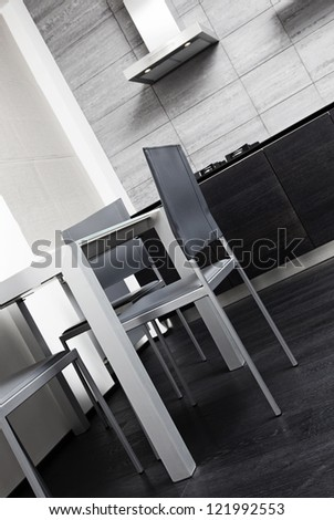 Fragment of modern minimalism style kitchen with dining table - stock photo