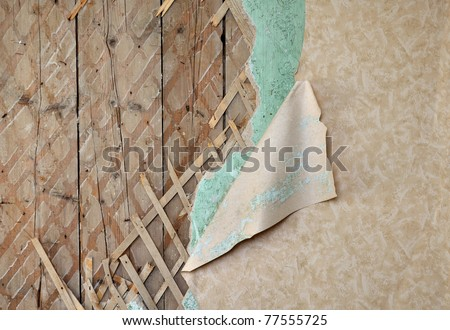 Fragment of old destroyed wall with jagged wallpaper and lath in abandoned house - stock photo