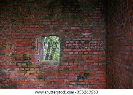 Fragment of old ruins built with red bricks and window with tree  - stock photo
