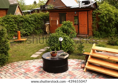fragment of private country garden with house and tile path, springwell and green lawn - stock photo