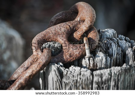 Fragment of rusty metal chain railing on old weathered wooden post in Key West harbor, Florida. Marina details. - stock photo