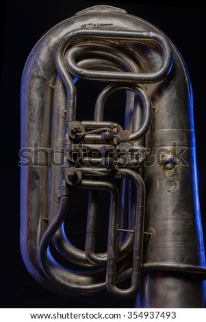 fragment of silver tuba isolated on black background - stock photo