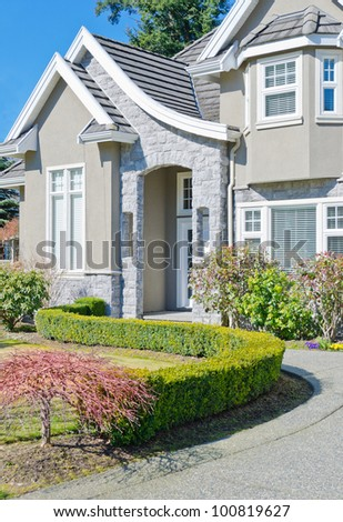 Fragment of the big luxury  home with nicely trimmed bushes at the doorway  in the suburbs of Vancouver, Canada - stock photo