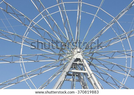 Fragment of the ferris wheel against the blue sky - stock photo