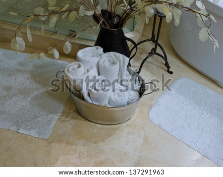 Fragment of the interior of the luxury modern bathroom with marble floor and some decoration. Some rolled towels in the zinc bucket. - stock photo