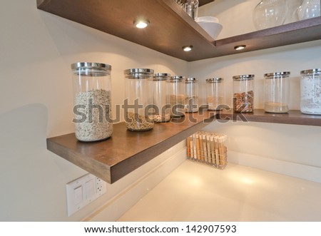 Fragment of the luxury modern kitchen with some shelves with jars, cans in the corner. Interior design. - stock photo