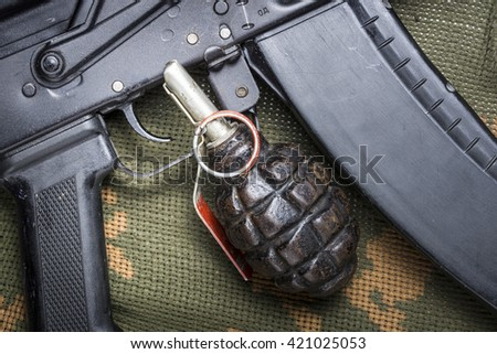 Fragmentation grenade, and Kalashnikov rifle, on camouflage clothing - stock photo