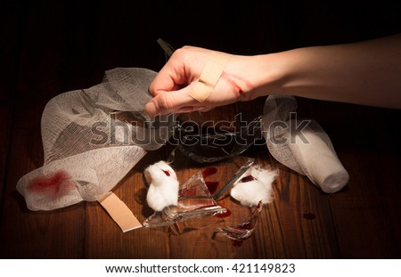 Fragments of broken glass, a wounded hand, bandages and adhesive tape on a black background. - stock photo