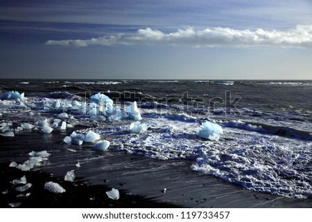Fragments of icebergs broken on a black volcanic beach Iceland - stock photo