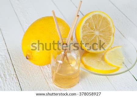 Fragrance sticks or bottle Scent diffuser with Lemon on wooden background.   - stock photo