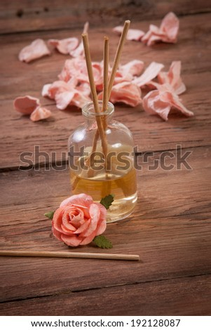 Fragrance sticks or Scent diffuser with rose flowers on wooden background - stock photo