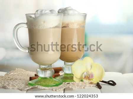 Fragrant coffee latte in glasses cups with spices, on wooden table - stock photo