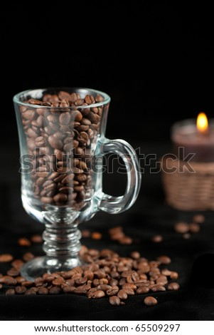 Fragrant fried coffee beans in the glass and lightning candle over black - stock photo