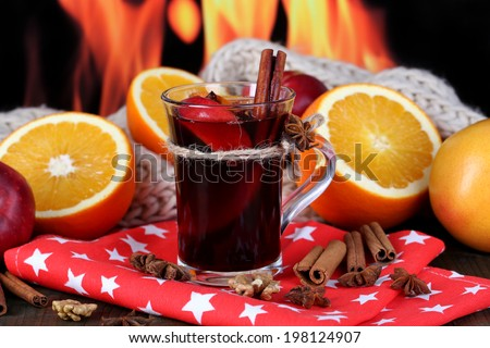 Fragrant mulled wine in glass on napkin on fire background - stock photo