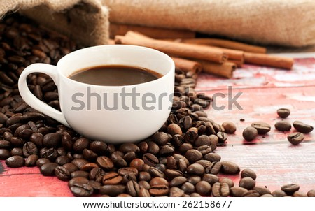 Fragrant, natural coffee in a cup standing on a wooden table in the coffee beans - stock photo