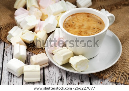 Fragrant, natural coffee in a cup standing on a wooden table. next to the coffee on a saucer, is a small marshmallows - stock photo