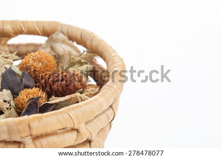 Fragrant natural potpourri with dried flowers, leaves and spices in a basket on white background  - stock photo