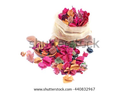 Fragrant natural potpourri with dried flowers, leaves and spices spilling out of a rectangular bag onto a white background for that special natural fragrance   - stock photo