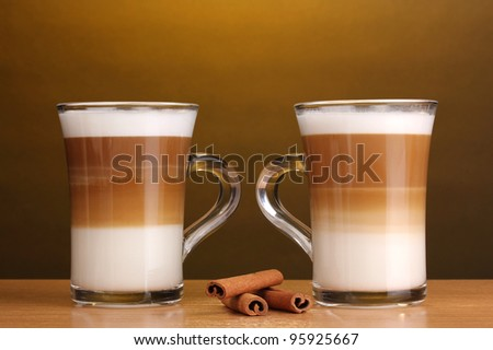Fragrant ?offee latte in glass cups and cinnamon on wooden table on brown background - stock photo