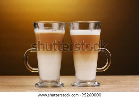 Fragrant ?offee latte in glass cups on wooden table on brown background - stock photo