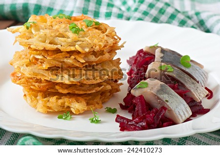 Fragrant potato pancakes  and herring with beetroot - stock photo