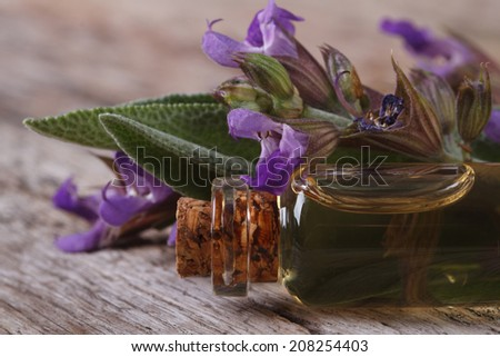 fragrant sage oil in a glass bottle on the table macro. horizontal