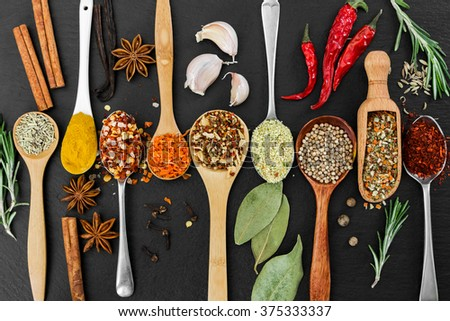 Fragrant seasonings and spices on black background. Top view. - stock photo