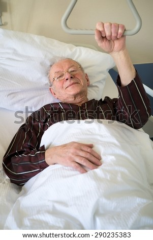 Frail senior man lying in a hospital bed on a ward recuperating from an illness or operation lying resting with his glasses on and eyes closed and a quiet smile - stock photo