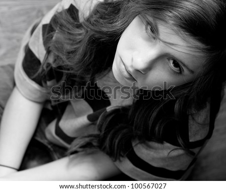 Frame filled black and white image of a beautiful teenage girl looking up with a serious expression - stock photo