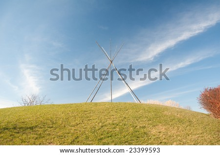 Frame for an American Indian tent in the nature under blue sky - stock photo
