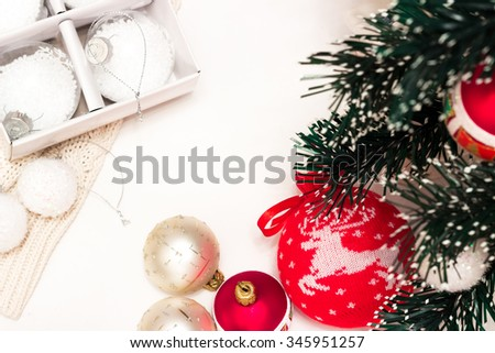 frame for text of Christmas toys on green fir branch namely big red ball with Christmas deer and the box with the new white balls and also red bow, garland - stock photo
