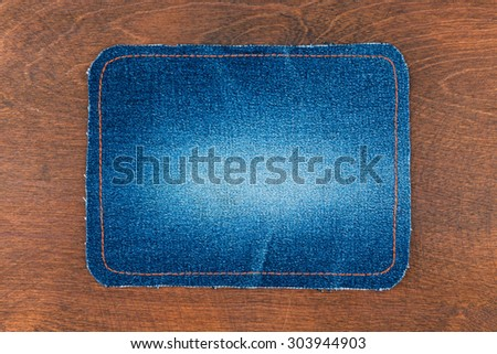 Frame for the text from a blue jeans fabric with the stitched lines of an orange thread, on a wooden background - stock photo