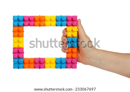 Frame made of colorful construction toy in female hand isolated on white background - stock photo