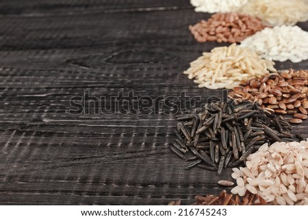 Frame made of colorful varieties of whole grain rice in a rustic wooden surface background - stock photo