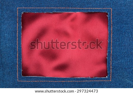 Frame made of denim fabric with yellow stitching on red silk, with space for your text - stock photo
