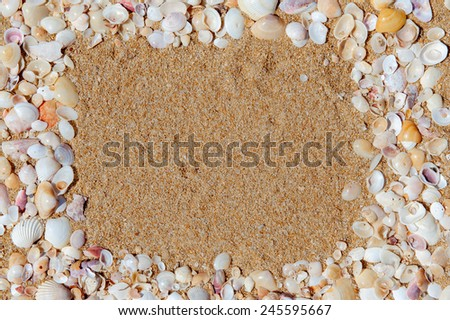 Frame made of seashells located on background of yellow sand - stock photo