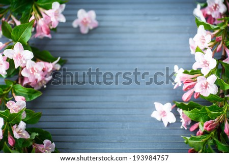 frame of beautiful pink flowers on wooden table - stock photo