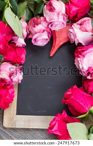 frame of blooming dark and  pink roses with heart  laying  on black  table - stock photo