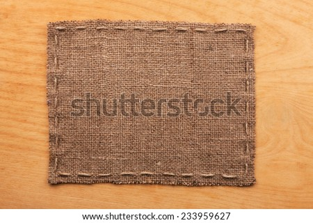 Frame of burlap, lies on a background of wood, with place for your text - stock photo