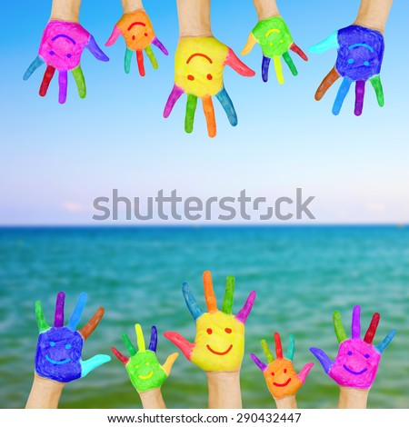 Frame of colorful hands painted with smiling faces against sea and sky background. Summer vacation concept. - stock photo