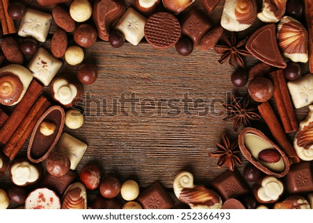 Frame of different kinds of chocolates on wooden table close-up - stock photo