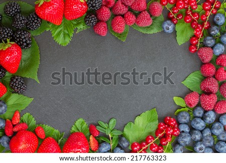 frame of fresh  berries with green,  leaves  on black stone background - stock photo