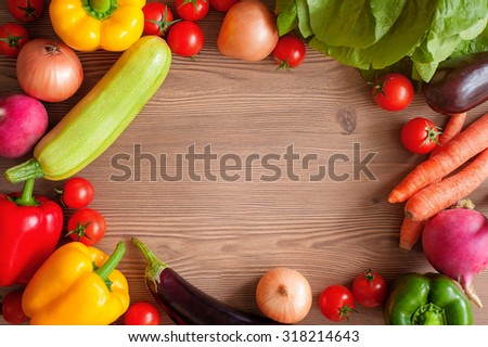 Frame of fresh colorful vegetables on wooden table, top view. Harvest, culinary, autumn background. Copy space. - stock photo