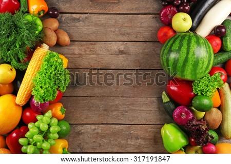 Frame of fresh vegetables on wooden background - stock photo