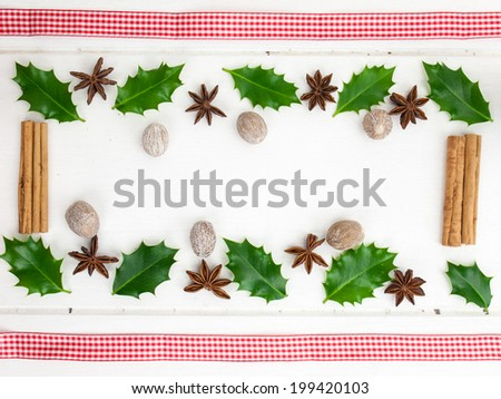 frame of holly leaves, nutmeg, cinnamon and star anise with checked red ribbon against a rustic white table top - stock photo