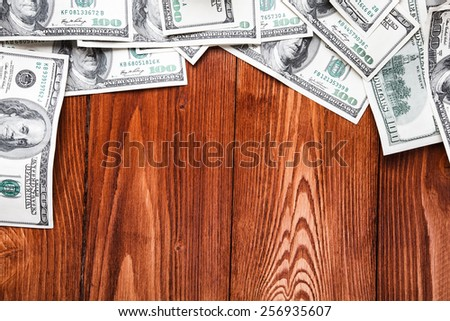 Frame of one hundred dollars banknotes lying on wooden table - stock photo
