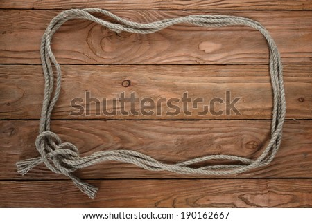 frame of rope on the background of wooden boards - stock photo