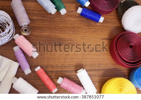 Frame of sewing threads, ribbons, sewing accessories on wooden surface. Place for an inscription. Copyspace. - stock photo