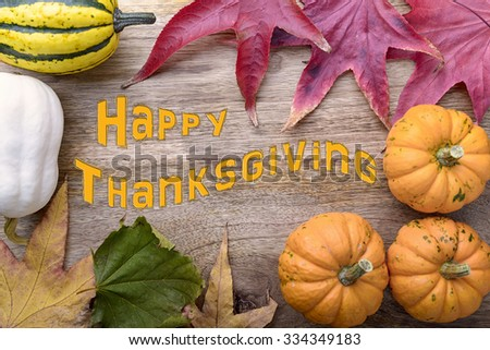 frame of small pumpkin and leaves on wood and happy thansgiving written - stock photo